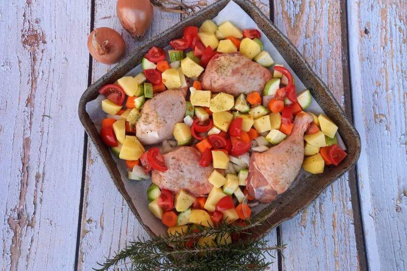Il pollo al forno con patate e verdure