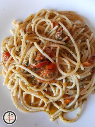 Spaghetti con bacon pesto di rucola e ciliegino