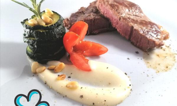 """Filetto di bovino affumicato con """"torretta"""" di zucchine grigliate, crema di parmigiano e pinoli tostati."""