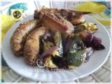 Salsicce e costine con zucchine e cipolla rossa al forno