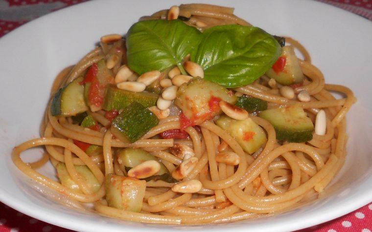 Spaghetti integrali con pomodori, zucchine e pinoli tostati