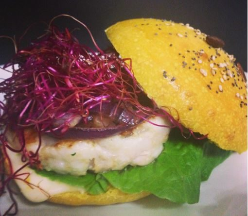 Burger buns alla curcuma farcito con Hamburger di pesce persico, cipolle di Tropea caramellate, lattuga e germogli di barbabietola
