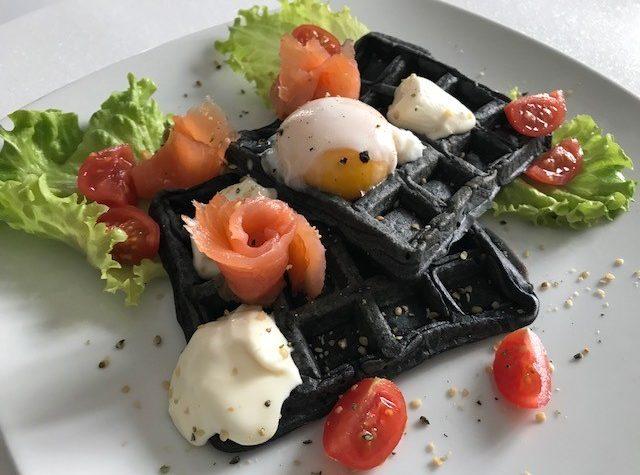 Waffle salati con farina nera, uovo in camicia, salmone affumicato e stracchino
