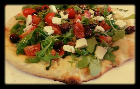 Pizza integrale con feta, rucola e pomodorini