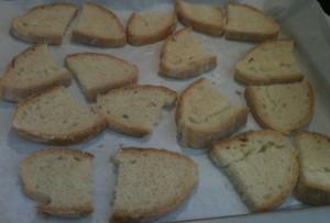 fette di pane tagliate in due disposte sulla placca da forno