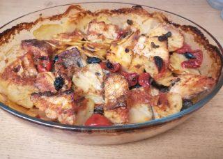 teglia di vetro con baccalà a pezzetti condito con aglio prezzemolo olive nere pomodoro capperi e patate