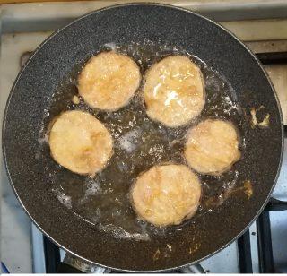 fette di melanzane impanate con uova e farina che friggono in olio bollente