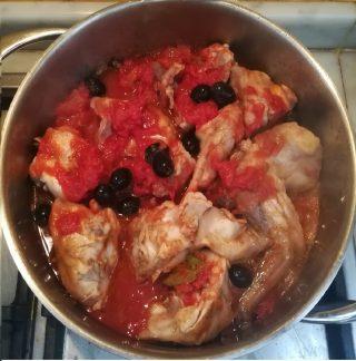 coniglio nel tegame che cuoce con olive olio e pomodoro a pezzettoni