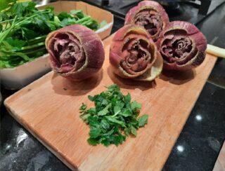 carciofi salati e pepati con ciufoo di prezzemolo e menta tritati sul tagliere
