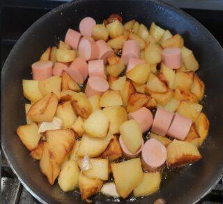 patate insieme ai wurstel che stanno friggendo