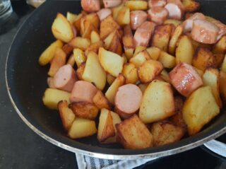 spadellata di wurstel e patatine pronti per essere mangiati