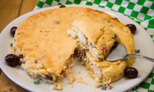 Torta di patate farcita con formaggio, pomodori e olive
